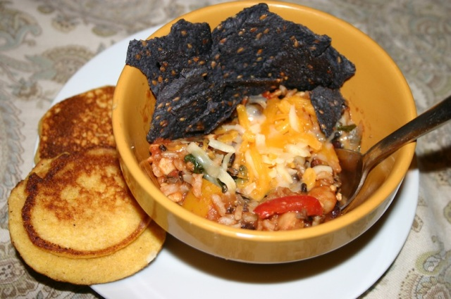 Chili with rice and cornbread cakes on the side